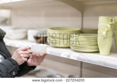 A Woman Choosing A Cup In A Crockery Store.