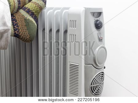 Winter Concept. Unknown Sick Man Placed His Feets On A Heater Getting Warm