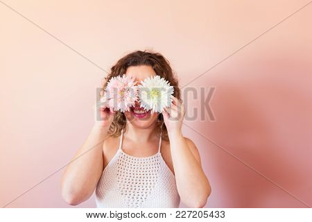 Beautiful Curly Woman Holding Pink Flower At Home. Hello Spring Concept.