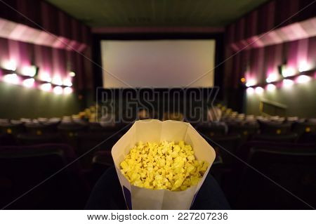 Cinema Hall With Big Screen And Pop Corn In Woman Hands