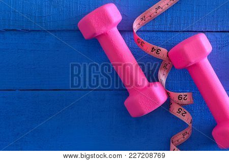 Dumbbells And Tape Measure On Wooden Background With Copy Space. Saturated Colors (blue, Pink). Spor