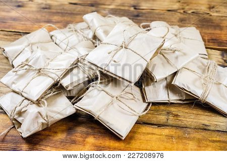 Close-up Many Gifts Wrapped Kraft Paper On Wooden Background