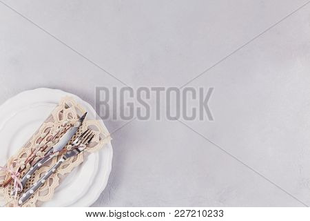 Easter Table Setting. White Plate, Cutlery, Lace Napkin And Pussy Willow Twigs On Light Stone Concre