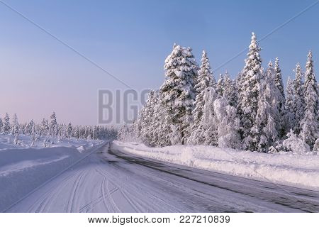 A Winter Highway Up North. Evening In Lapland, Snowy Landscape.