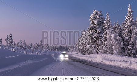 Traffic Along A Winter Highway Up North. Evening In Lapland, Snowy Landscape.