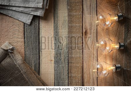 Top View Image With Bulbligt Garland And Canvas Bag On Raw Rustic Background.