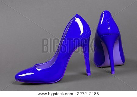Lacquered Blue High Heels Shoes On Gray Background.