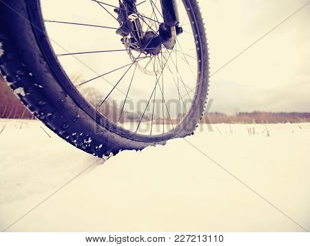 Winter Mtb Riding In Snowy Country. Low Ankle View To Wheel With Snow Mud Tyre. Melting Of Snow Flak