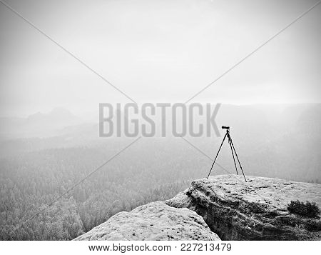 Tripod On The Peak Ready For Photogrpahy. Exposed Rocky View Point. Misty Rainy Autumnal Day In Wild