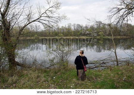 Girl Sitting On Stump In Front To Lake. Poland
