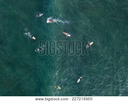 Several Surfers On The Surfboards On The Ocean Surface. Aerial Horizontal Photo.