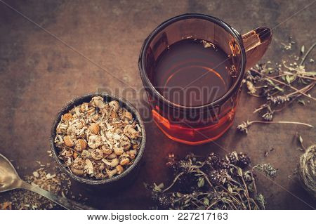 Cup Of Healthy Tea, Rustic Mortar Of Daisy Herbs, Dried Thyme On Table. Herbal Medicine.