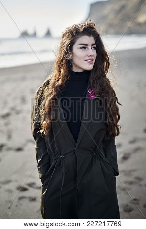 Cute Smiling Girl With Closed Eyes Is Posing On The Black Sand Beach On The Background Of The Rocky