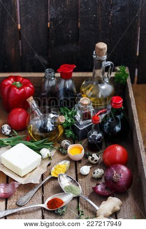 Set Of Bottles With Sauces, Oil And Vegetables In A Woden Box