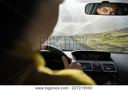 Man Is Driving A Car On The Country Roadway Between Brown Fields On The Background Of The Mountains