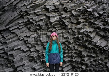 Attractive Girl In Glasses Is Posing On The Black Basalt Column Formation Background In Iceland. She