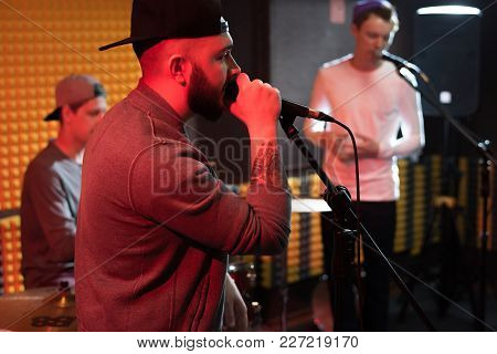 Side View Portrait Of Tattooed Hip-hop Musician Performing In Dim Recording Studio While Making New