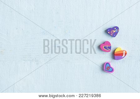 Multicolored Erasers In The Shape Of The Heart On Blue Background. Free Space For Text.
