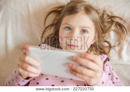 Top View Of Cute Little Girl With Tablet In Hand