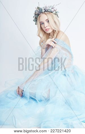 Blonde Woman With Wreath On Her Head And A Gentle Light Blue Transparent Dress On A White Background