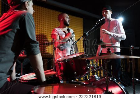 Portrait Of Modern Music Band Rehearsing In Recording Studio Lit By Dim Lights While Making New Albu