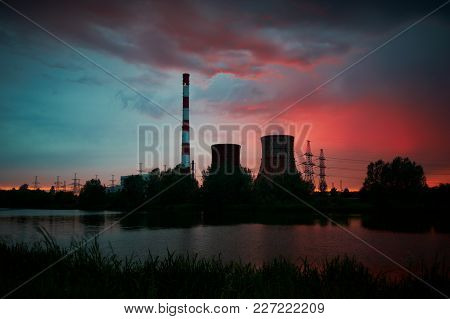 Silhouette Of Gas Turbine Electrical Power Plant With Cooling Towers Against Sunset Sky