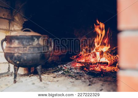 Cozy Flaming Fire In A Stone Fireplace With Jug