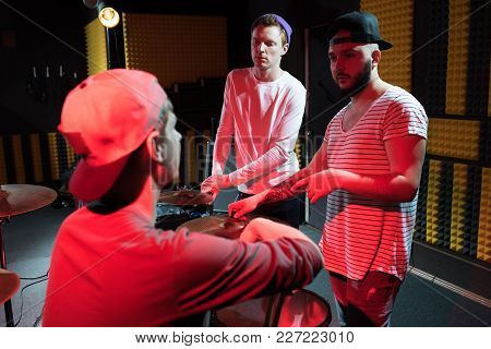 Portrait Of Three Musicians Discussing New Album While Rehearsing In Recording Studio, Lit By Red Li