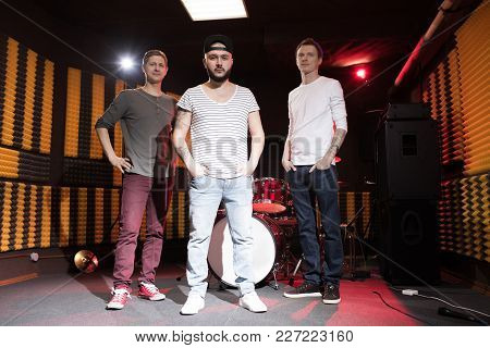 Full Length Portrait Of Modern Music Band Posing In Recording Studio And Looking At Camera With Drum