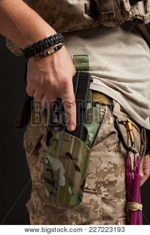 Close-up Of A Gun That Properly Holds A Man In A Military Desert Uniform And Body Armor On A Black B