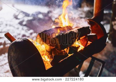 Barbecue Grill In The Snow-covered Complex In Smoke With Fire