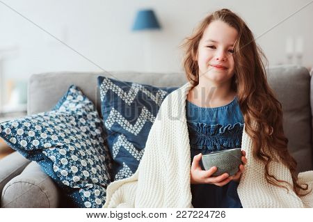 child girl drinking hot tea to recover from flu. Healing kids and protect immunity from seasonal vir