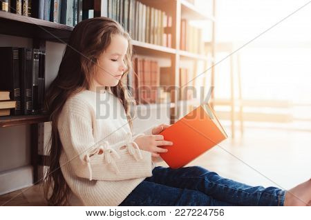 Happy Smart Schoolgirl Reading Books In Library Or At Home. Kids Early Learning And Education Concep