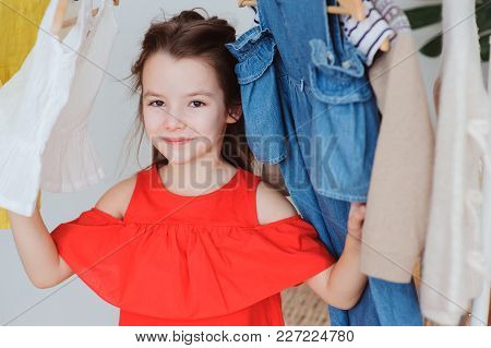 Cute Little Child Girl Choosing New Modern Clothes In Her Wardrobe Or Store Fitting Room. Kid Fashio