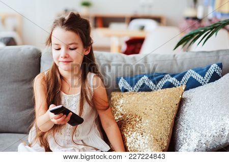 Child Girl Watching Tv At Home On Cozy Couch. Modern Scandinavian Interior, Kids And Television Conc