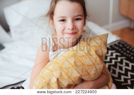 Happy Child Girl Sitting On Bed And Hugs Pillow, Waking Up In Early Morning Or Going To Sleep. Kid I