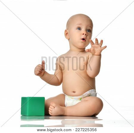Infant Child Baby Boy Toddler Sitting Naked In Diaper With Green Brick Toy Looking Up At The Corner