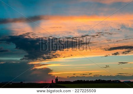 A Juicy Orange Sunset With A Crimson Glow A Huge Blue Sky And Gray Clouds, Over A Green Field, A For