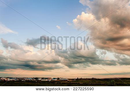 Orange And White Clouds, Highlighted By The Rising Sun, Against The Blue Sky, Farm Buildings And Gre