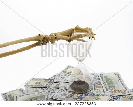 Skeleton Fingers Holding The Top Of Sand-glass Placed On Dollars. Time Is Up. Concept Of Time - Mone