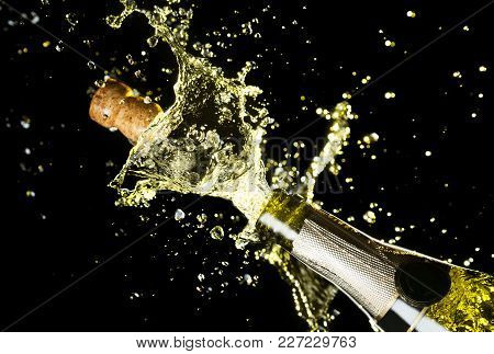 Close Up Image Of Champagne Cork Flying Out Of Champagne Bottle. Celebration Theme With Explosion Of