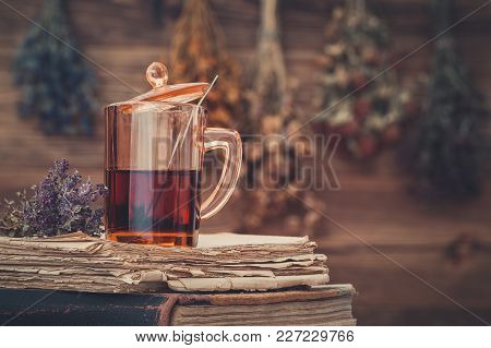 Cup Of Healthy Tea Or Herbal Tincture On Stack Of Old Books. Hanging Bunches Of Medicinal Herbs On B