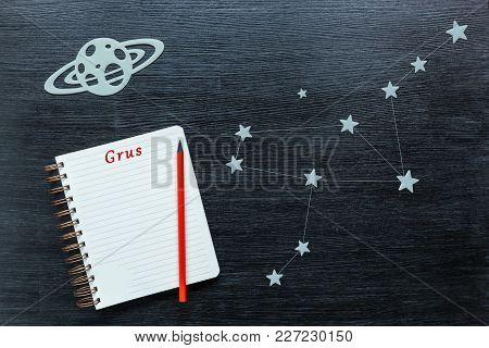 Zodiacal Star, Constellations Grus On A Black Background With A Notepad And Pencil.