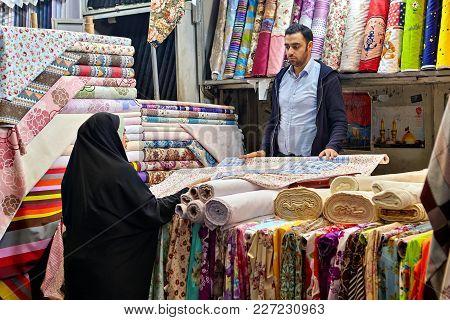 Tehran, Iran - April 29, 2017: Muslim Woman Dressed In Black Chador Chooses Cloth In Tehran Grand Ba