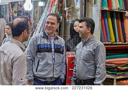 Tehran, Iran - April 29, 2017: Three Men Trading In The Market Are Talking Near A Textile Store.