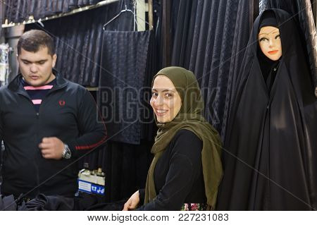 Tehran, Iran - April 29, 2017: A Smiling Muslim Girl Trades In A Black Cloth For A Religious Veil In