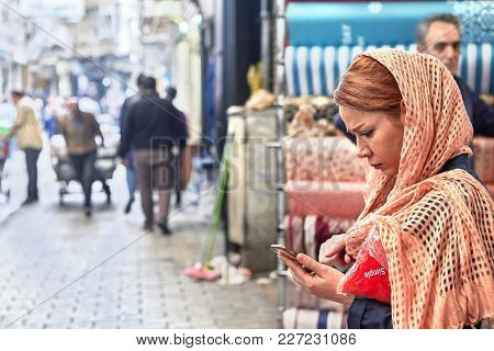 Tehran, Iran - April 29, 2017: One Young Woman, Dressed In Pink Hijab, Looks At The Screen Of The Sm