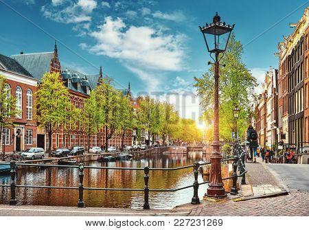 Bridge over channel in Amsterdam Netherlands houses river Amstel landmark old european city spring landscape.