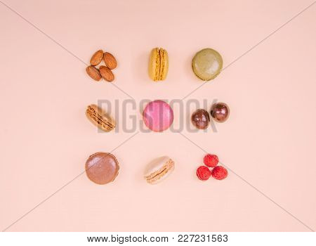 Colorful Macaroons On The Pink Background. Creative Flat Lay Food Concept.