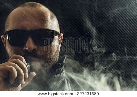 Portrait Of Smoker Man In Sun Glasses Vaping E-cigarette With E-liquid. Vape Concept, Copy Space, Da